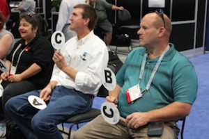 "Brenda Breighner, Jim Snyder, and Wayne Breighner played in the booth's live demo of the game, ""Are You Smarter Than a FenestrationMaster?"" at GlassBuild America in Las Vegas in 2014."